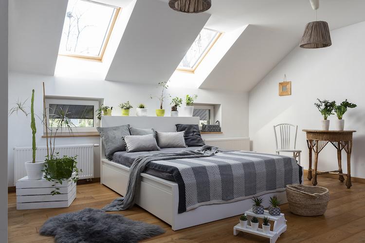 Una camera da letto in mansarda sotto i lucernai